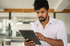 Amerikaanse bedrijfsmens die digitale tablet gebruiken op het kantoor Royalty-vrije Stock Fotografie