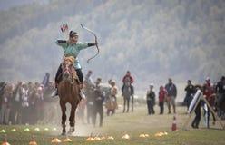 Amerikaanse dame die bij boogschieten op horseback bij Wereldnomade G concurreren stock foto