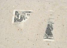 Amerikaanse dollar onder zand stock fotografie