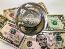 Amerikaanse dollarbankbiljet, het muntstuk van de kwartdollar en glasbal stock foto's