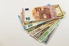 Amerikaanse dollarrekeningen en Euro uitgespreid die rekeningen op witte achtergrond worden gemengd Stock Foto's