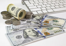 100 Amerikaanse dollars bankbiljetten en geldmuntstukken met keyboar computer Royalty-vrije Stock Afbeelding