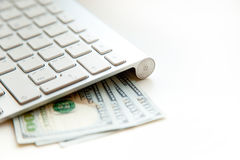 100 Amerikaanse dollars bankbiljetten en geldmuntstukken met keyboar computer Stock Fotografie