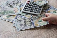 Amerikaanse dollars, calculator en hand op een houten achtergrond stock foto