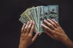 Amerikaanse dollars in de handen, vrouwen die geld tellen Royalty-vrije Stock Afbeelding