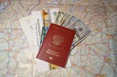 Amerikaanse dollars en buitenlands paspoort op de kaartachtergrond stock foto