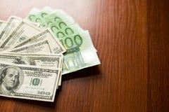Amerikaanse dollars en euro bankbiljettentextuur donkere houten Achtergrond van dollar honderd en euro rekeningen stock afbeelding