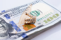 Amerikaanse 100 dollarsbankbiljetten en een kroon Stock Foto's