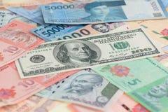 Amerikaanse honderd dollarsrekeningen en Aziatische muntenachtergrond Royalty-vrije Stock Afbeeldingen