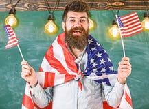 Amerikaanse leraarsgolven met Amerikaanse vlaggen De mens met baard en snor op gelukkig gezicht houdt vlaggen van de V.S., in kla stock afbeeldingen