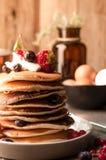 Amerikaanse pannekoeken in stapel met zure room, verse aardbeien en bosbessen royalty-vrije stock afbeelding