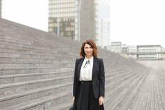 Amerikaanse secretaresse die zich op treden met zak en hoge gebouwen op achtergrond bevinden Royalty-vrije Stock Afbeeldingen