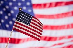Amerikaanse stuk speelgoed vlag over andere grote vlag. Stock Afbeeldingen