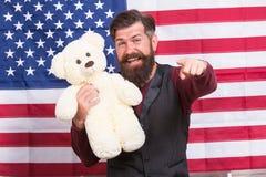Amerikaanse vakantie Van de de greepteddybeer van mensen gebaarde hipster Amerikaanse de vlagachtergrond Kinderverzorging Nog kin stock foto
