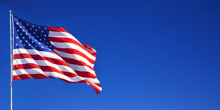 Amerikaanse vlag die in blauwe hemel 1 golft stock fotografie