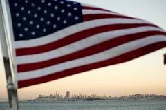 Amerikaanse vlag die boven San Francisco vliegt stock afbeelding