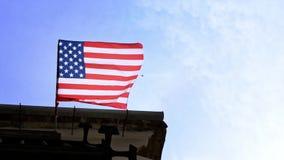 Amerikaanse vlag die in de wind op vlaggestok bij de stad van Amerika golven De banner van de V.S. - Dan stock footage