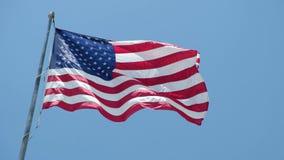 Amerikaanse vlag die in de wind tegen blauwe hemel golven stock video