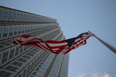 Amerikaanse vlag die in de wind tegen een wolkenkrabber fladderen stock foto's