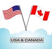 Amerikaanse vlag die met Canadese vlag wordt gekruist Stock Foto's