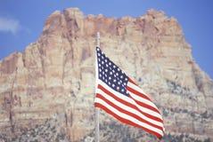 Amerikaanse Vlag die voor Berg, Zuidwestenverenigde staten vliegen Stock Foto