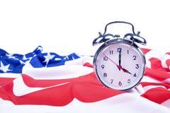 Amerikaanse vlag en wekker die op wit wordt geïsoleerdk Royalty-vrije Stock Afbeeldingen