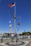 Amerikaanse vlag en zeevaartvlaggen die bij Woodcleft-Promenade in Freeport, Long Island vliegen Stock Foto's