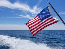 Amerikaanse vlag op boot met kielzog stock foto's