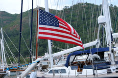 Amerikaanse vlag op een mastjacht in de haven op een achtergrond van hil Royalty-vrije Stock Fotografie