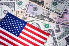 Amerikaanse vlag op geassorteerde bankbiljetten Geld, contant geldachtergrond Pen, oogglazen en grafieken royalty-vrije stock foto