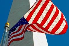 Amerikaanse vlag tegen Washington Monument en blauwe hemel stock fotografie