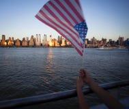 Amerikaanse vlag tijdens Onafhankelijkheidsdag op Hudson River met een mening bij de Stad van Manhattan - van New York - Verenigd Stock Afbeelding