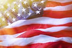 Amerikaanse vlagachtergrond Helder aangestoken Amerikaanse vlag Zonlicht, sunflare op de rechterkant royalty-vrije stock foto