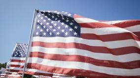 Amerikaanse vlaggen die met een blauwe hemelachtergrond golven De achtergrond van de onafhankelijkheid Day stock footage