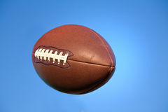 Amerikaanse voetbal in blauwe hemel met het knippen van weg. stock fotografie