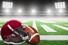Amerikaanse Voetbal en Helm op Gebied met Stadionlichten en Exemplaarruimte royalty-vrije stock foto's