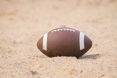 Amerikaanse voetbal in het zand op het strand stock foto's