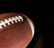 Amerikaanse voetbal tegen een zwarte achtergrond royalty-vrije stock foto's