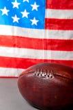 Amerikaanse voetbalbal en oude glorievlag stock foto's