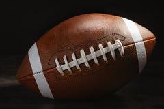 Amerikaanse voetbalbal op lijst tegen donkere achtergrond stock afbeeldingen