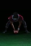 Amerikaanse voetbalster die houdend een bal op gras met beide handen buigen Royalty-vrije Stock Fotografie