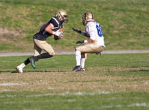 Amerikaanse Voetbalster die met de Bal tijdens een Spel lopen stock foto