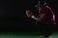 Amerikaanse voetbalsterzitting op tenen die een bal met beide handen houden Royalty-vrije Stock Foto's