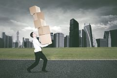 Amerikaanse zakenman opheffende dozen in de weg Stock Afbeelding