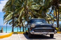Amerikaanse zwarte klassieke die auto onder palmen wordt geparkeerd Royalty-vrije Stock Afbeeldingen