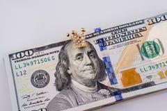 Amerikan 100 dollarsedlar och en krona Arkivfoton