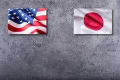 Amerikan- och Japan flaggor USA- och Japan flagga på konkret backgro Arkivbilder