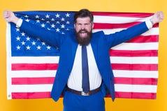 Amerikan vid födelse Rebell vid val Stilig skäggig man för säker affärsman i den formella dräkthållflaggan USA lyckat arkivbild