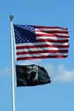 Amerikaner- und KRIEGSGEFANGEN-Markierungsfahnen gegen einen blauen Himmel Stockbilder
