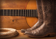Amerikanische Countrymusik mit Gitarren- und Cowboyschuhen auf hölzernem Text Lizenzfreie Stockbilder